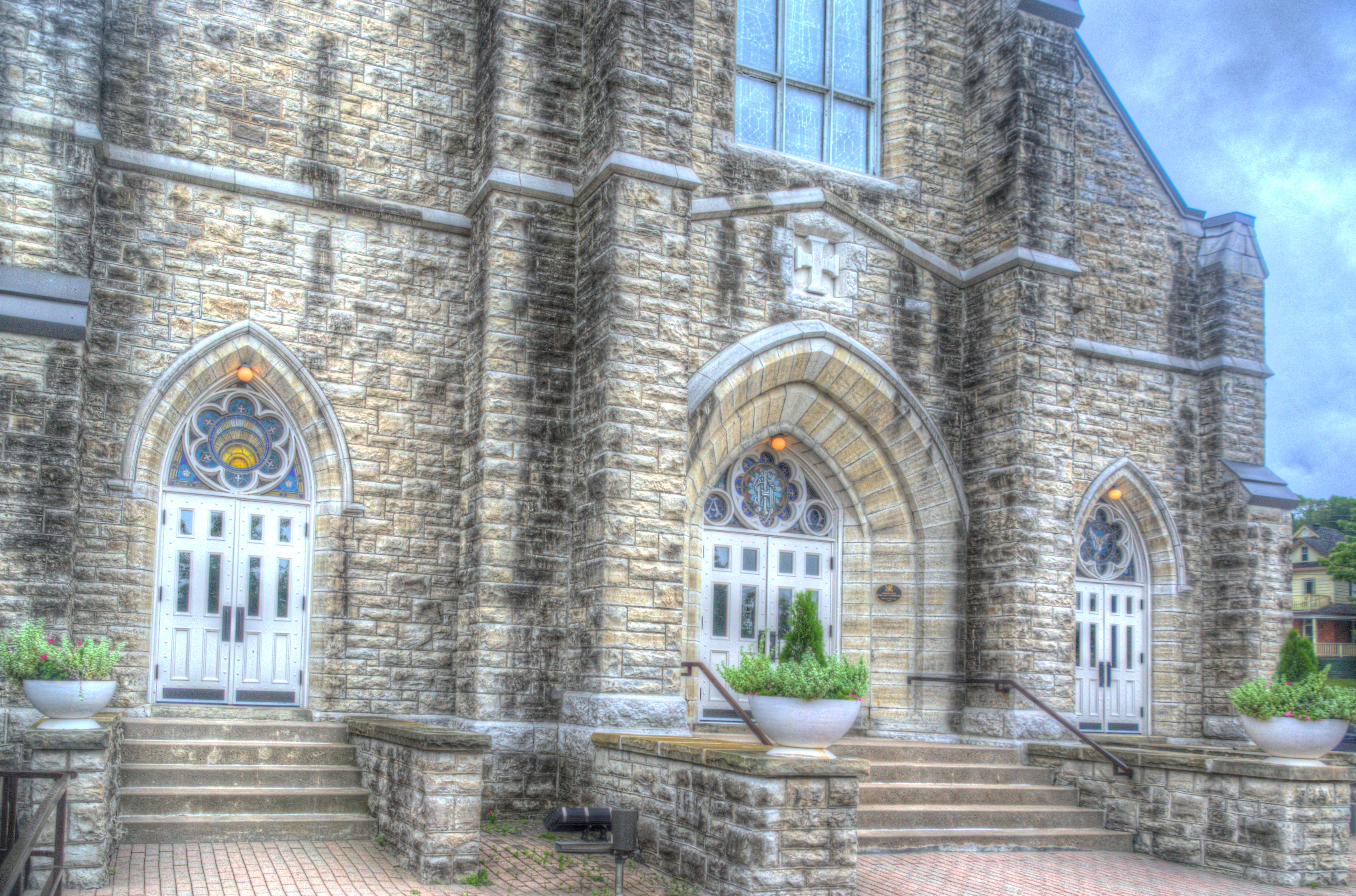 Outside image of St. Margaret's beautiful front doors with a stain glass above the doors.