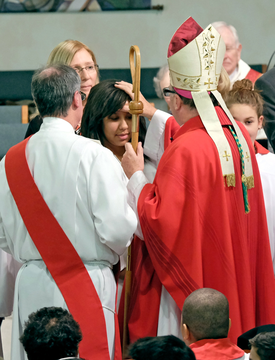 A Bishop confirming a young women with a deacon to his left and a female sponsor behind the confirmandi.